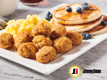 A fluffy stack of blueberry pancakes with a side of Jimmy Dean® Sausage Tots and scrambled eggs as irresistible sides.